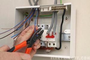Электрик монтирует электрический щиток